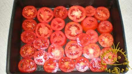 Смазываем растительным маслом противень, укладываем на него помидоры, порезанные кружочками толщиной около 1-го см